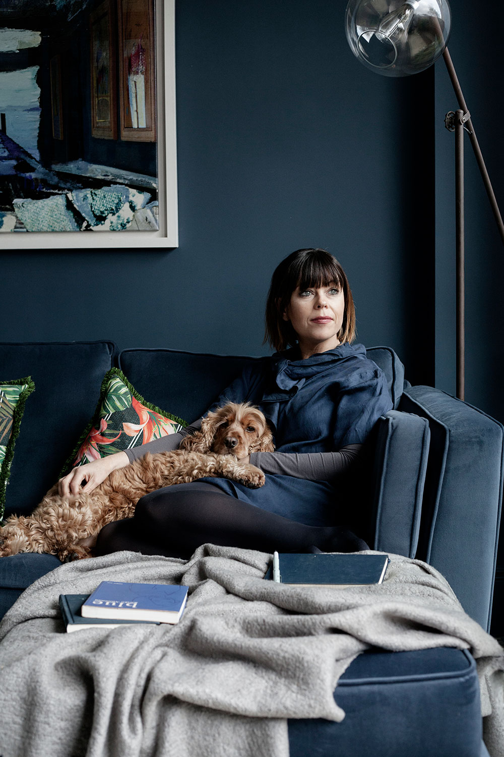 Interior designer Caroline Flannery of Interiors by Caroline at home in Clontarf Dublin with her dog on custom made sofa